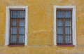 Two old windows on the yellow wall