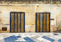 Two old wooden doors on marble brick wall. Colored tiled floor