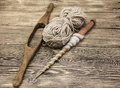 Two old wooden spindle with a ball of wool thread for the manufacture of woolen threads on a wooden background Royalty Free Stock Photo
