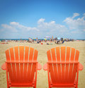 Two orange beach chairs in sand are looking at the crowded with people on vacation for a getaway or relaxation concept Stock Photography