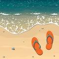Two orange beach slippers on a sandy beach near the edge of the surf