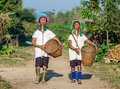 Two Padaung women in traditional dress walk along a village street with wicker baskets in their hands. Royalty Free Stock Photo