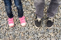 Two pairs of feet in sneakers, adults and children, are on the pebble Royalty Free Stock Photo