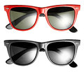 Two pairs of modern trendy sunglasses one with a black frame and the other in red for a fashionable summer clothing accessory Royalty Free Stock Images