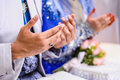 Two pairs newly wedded couple s hands raised prayer Stock Photography