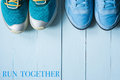 Two pairs of running sneakers on blue background Royalty Free Stock Photo
