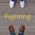 Two pairs of shoes standing on walkway with fighting Stock Photography