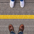 Two pairs of shoes standing on walkway with yellow line separate Royalty Free Stock Photo