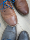 Two pairs of shoes toe to toe on  a wooden floor Royalty Free Stock Photo