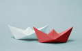 Two paper boats competing with each other red and white ships sailing on gray background rivalry business success and efficiency Royalty Free Stock Image