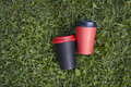 Two paper cups with coffee to take away, red and  black cup on green grass outdoor breakfast. Royalty Free Stock Photo