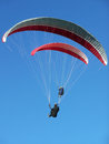 Two paragliders paragliding against blue sky Stock Photography