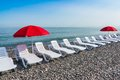 Two parasol and plastic beach chairs Royalty Free Stock Photo