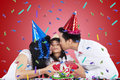 Two parents giving a gift for child portrait of asian kissing their while in birthday party Royalty Free Stock Photography