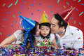 Two parents kiss their child in birthday party Royalty Free Stock Photo