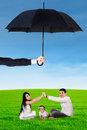 Two parents and their child playing under umbrella Royalty Free Stock Photo