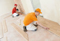 Two parquet carpenter workers installing wood board during flooring work Royalty Free Stock Photo