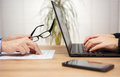 Two partners are examining and reviewing document in office wom woman is using laptop for comments Stock Photos