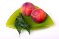 Two peaches with green leaves on a triangular plate Royalty Free Stock Photo