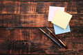Two pens with paper notes on brown background Royalty Free Stock Photo