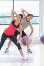 Two people doing power fitness exercise at yoga class portrait of smiling in studio Stock Images