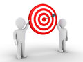 Two people holding target with arrow at the center Royalty Free Stock Photo
