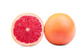 Two perfectly round grapefruits,  on a white background. Delicious fresh whole and cut grapefruits full of nutrients.