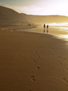 Two persons go into the distance across the sand at sunset Stock Images