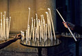 Two persons offering a candle hands of in catholic church in dark interior Royalty Free Stock Image