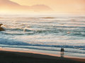 Two persons walking on beach at sunset Royalty Free Stock Image