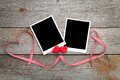 Two photo frames over wooden background with red ribbon and candy hearts Stock Photo