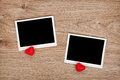 Two photo frames and small red candy hearts on wooden background Royalty Free Stock Photo