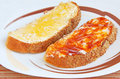 Two pieces of bread with butter and jam Stock Photography