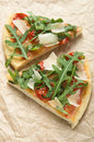 Two pieces of pizza with arugula rucola tomatoes and parmeasan Royalty Free Stock Photography