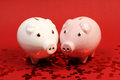 Two piggies bank in love standing on red background with red shining heart glitters stading horizontal Royalty Free Stock Image