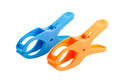 Two plastic spring clamps isolated over white background closeup of blue orange Royalty Free Stock Photo