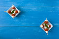 Two plates of skewers with mozzarella, cherry tomatoes and basil Royalty Free Stock Photo