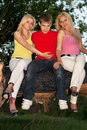 Two playful blonde and young man men sitting on a tree branch Royalty Free Stock Photo