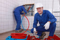 Two plumbers working one plumber is connecting pipes Stock Photos