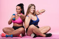 Two plump women posing with dumbbells on floor Royalty Free Stock Photo