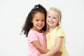 Two pre school girls hugging one another smiling Stock Photos