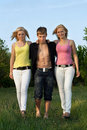Two pretty blonde and young man walking Stock Images