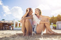 Two pretty female friends sitting together on beach laughing Royalty Free Stock Photo