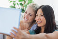 Two pretty friends taking photo with tablet pc at home on couch Royalty Free Stock Photos