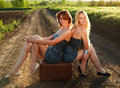 Two pretty girl sitting on suitcase at countryside lonely road in sunset rays Royalty Free Stock Photos