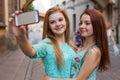 Two pretty girls taking selfie. Urban background. We love selfie Royalty Free Stock Photo
