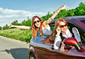 Two pretty happy girls in the car concept of carefree roadtrip Royalty Free Stock Image