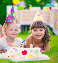Two pretty little girls celebrating birthday on green grass Royalty Free Stock Photography