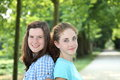 Two pretty teenage girls standing back to back in a wooded park smiling at the camera Royalty Free Stock Photos