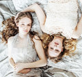 Two pretty twin sister blond curly hairstyle girl in luxury house interior together, rich young people concept Royalty Free Stock Photo